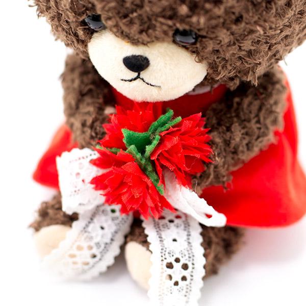 レースで束ねた赤いお花のブーケを持って