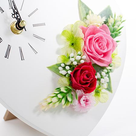 赤とピンクのプリザーブドフラワーのバラがあしらわれた時計です。